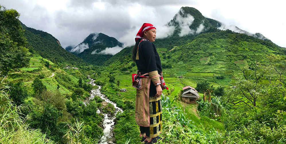 Native standing in beautiful mountain scenery from our North Vietnam Tribal Culture Tour